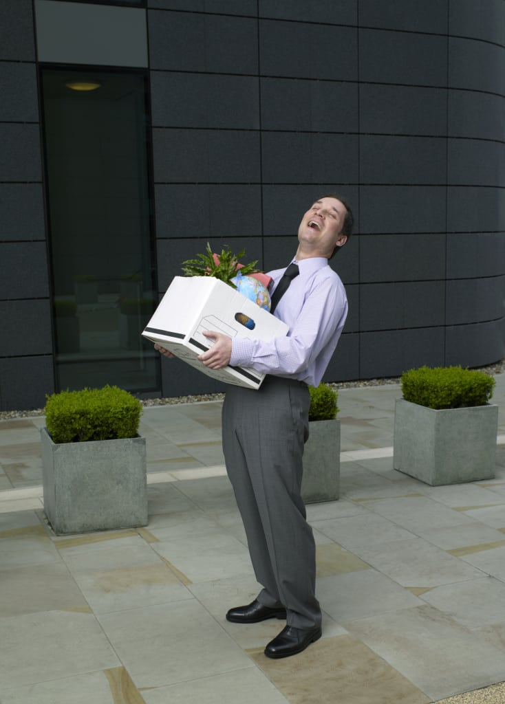Businessman outside building holding box of belongings, laughing